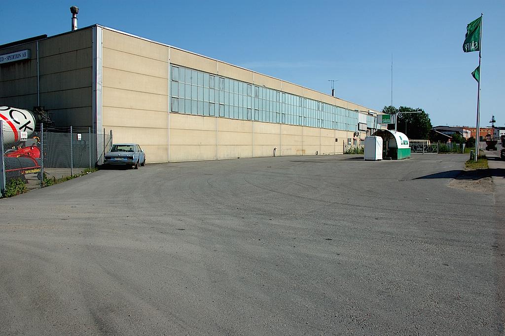 Öde asfaltsplan, en skrotbil och en sommarstängd lagerlokal