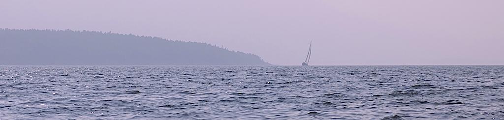Segelbåt mot horisonten i soldis