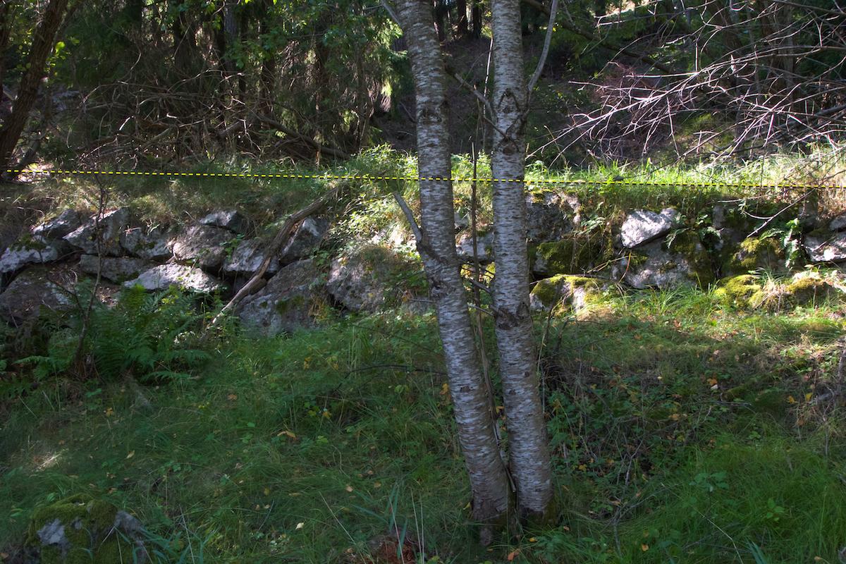 Vägbank i profil med rejäla stena i fundamentet.